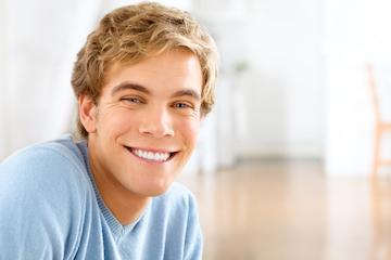 Man smiling in blue shirt after he whitened his teeth