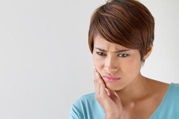 Woman holding jaw in pain | Dentist Fontana CA